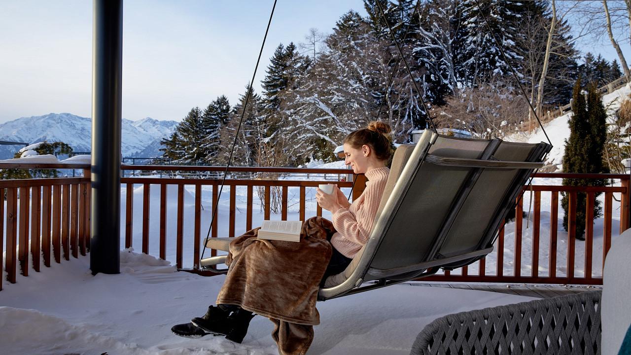 Frau liest im Winter aus dem Raum vor Hotel Chalet Mirabell Hafling