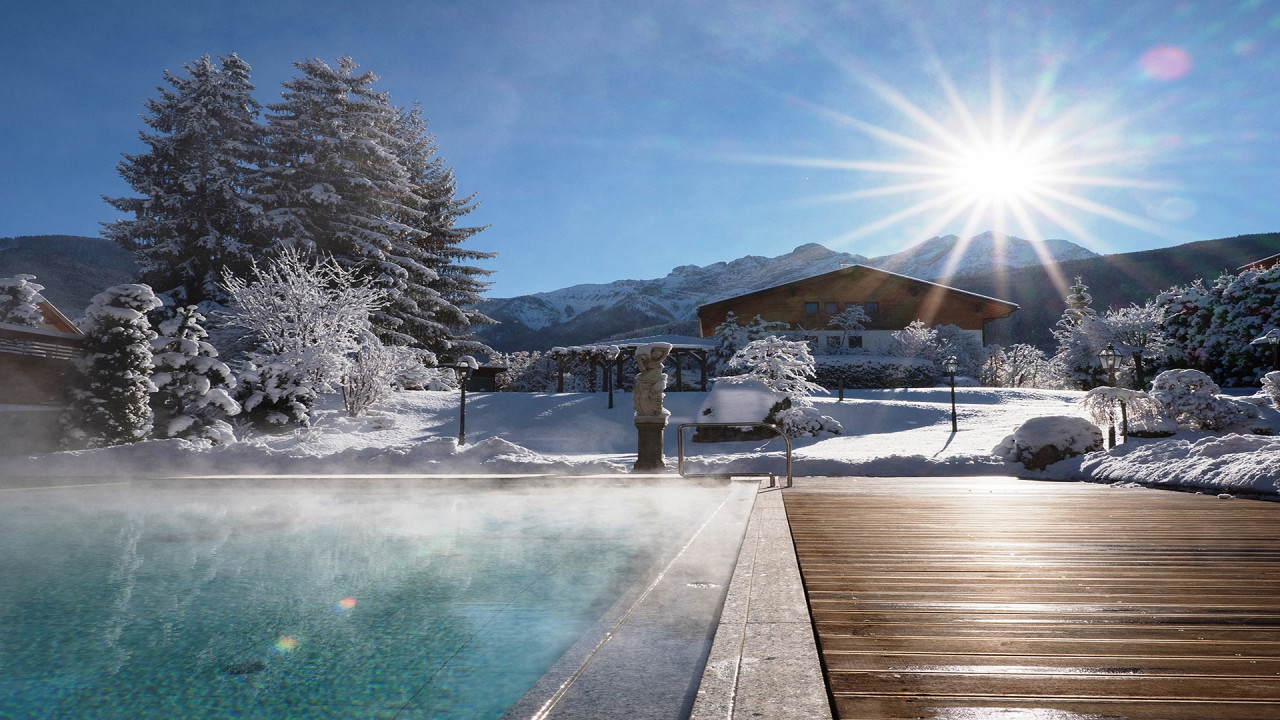 Outdoor swimming pool in winter Mirabell Dolomites Hotel Valdaora