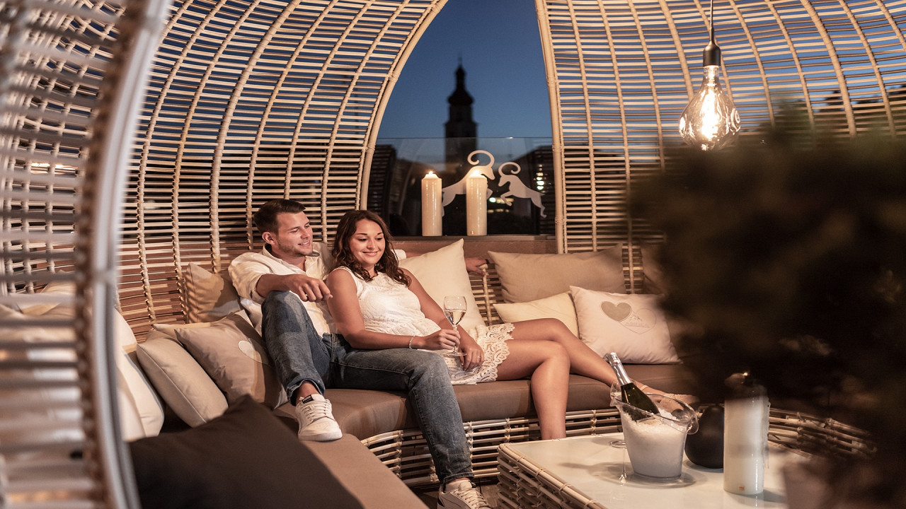 Couple relaxing on the outdoor terrace Abinea Hotel Castelrotto